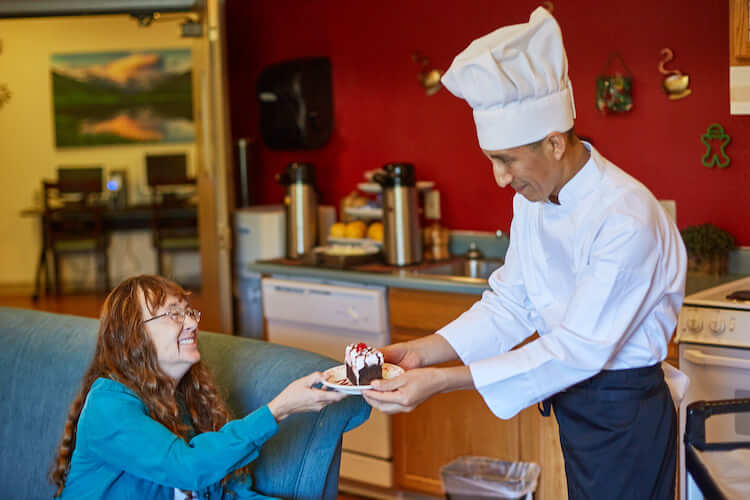 chef giving resident a cake