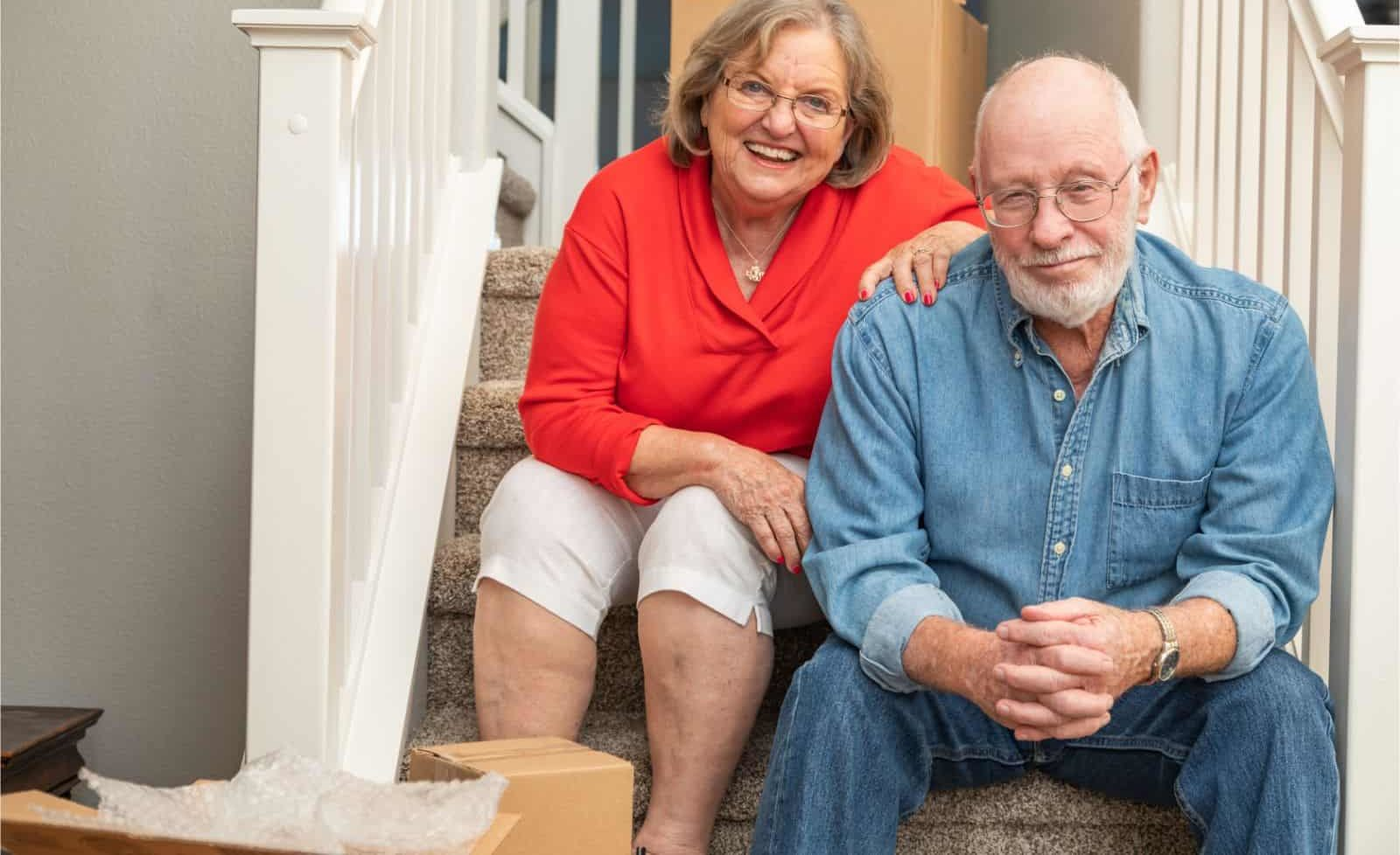Seniors sitting on steps with moving boxes
